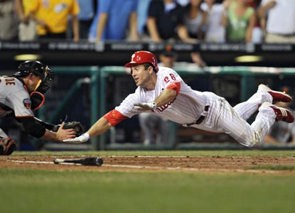 Philadelphia's Chase Utley dives home, eluding Eli Whiteside's tag to complete an inside-the-park home run. (Getty Images)