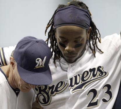 Rickie Weeks is helped off the field by Brewers manager Ron Roenicke after injuring his ankle running to first base. (AP)