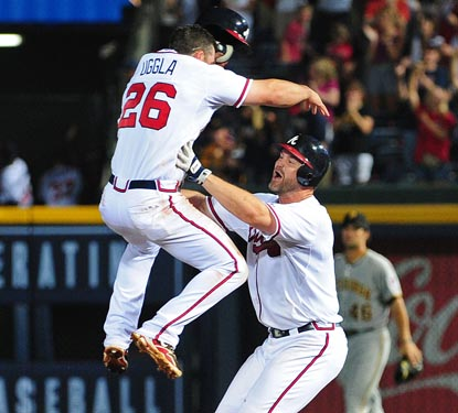 Dan Uggla (18-game hitting streak) celebrates Atlanta's victory by leaping into the arms of 10th inning hero David Ross. (Getty Images)