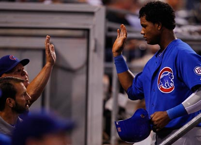 Starlin Castro is congratulated by manager Mike Quade in the Cubs' dugout after scoring in Chicago's victory. (Getty Images)