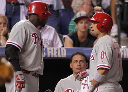 Shane Victorino accepts congratulations from Ryan Howard after his 10th-inning home run gives Philly its winning margin. (Getty Images)