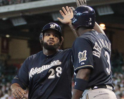 Prince Fielder accepts congratulations from Brewers teammate Yuniesky Betancourt after scoring in the third inning. (Getty Images)