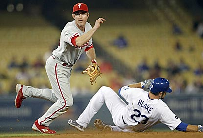 Despite Casey Blake's efforts, Chase Utley successfully pivots and completes a double play that ends the seventh inning.  (AP)