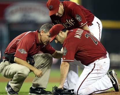 Jason Marquis confers with Arizona's medical staff before leaving the game after taking a line drive off his right shin. (Getty Images)