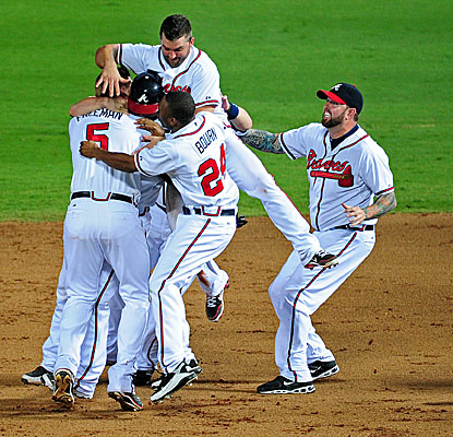 Atlanta Braves players mob teammate Freddie Freeman after his game-winning run off Giants closer Brian Wilson. (Getty Images)