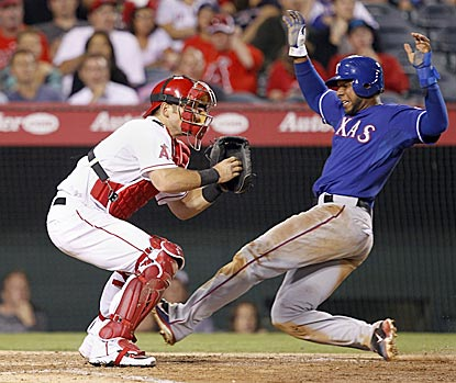 Elvis Andrus slides past Jeff Mathis to score his second run of the night on Michael Young's sacrifice fly in the sixth inning. (AP)