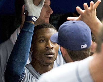 B.J. Upton receives congratulations in the Rays dugout after his three-run homer in the seventh inning. (AP)