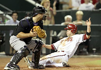 Arizona's Aaron Hill slides past Colorado catcher Chris Iannetta during the Diamondbacks' four-run sixth inning.  (Getty Images)