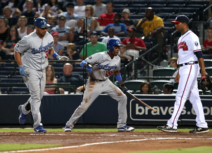 Dee Gordon (center) scores the go-ahead run in the top of the 10th on a sacrifice fly hit by Juan Rivera. (Getty Images)