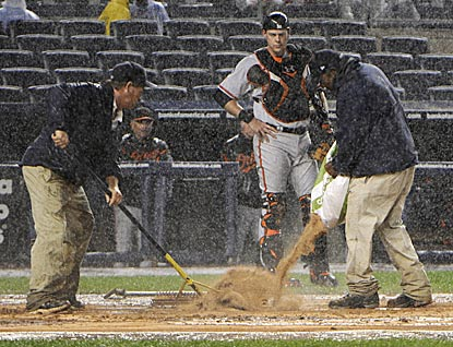 Baltimore catcher Matt Wieters waits while the Yankees grounds crew applies drying agent during the middle of the fifth inning. (AP)