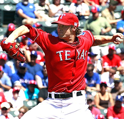 C.J. Wilson pitches eight shutout innings for the Rangers, striking out 11 A's and walking one. (Getty Images)