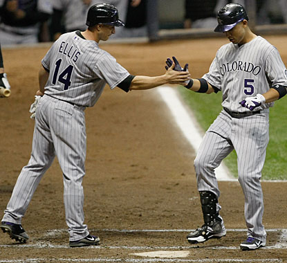 Carlos Gonzalez gets cheers from Mark Ellis at home plate after a homer in the third inning. (Getty Images)