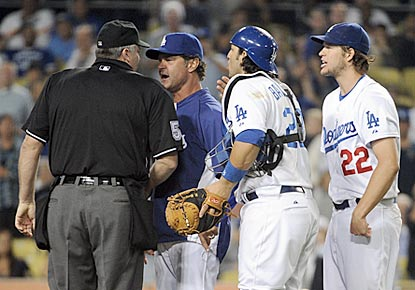 Dodgers manager Don Mattingly and catcher Rod Barajas plead Clayton Kershaw's case to home plate umpire Bill Welke.  (Getty Images)
