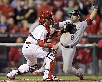 Nick Punto slides past Phillies catcher Carlos Ruiz to score on Albert Pujols' double in the seventh inning.  (AP)