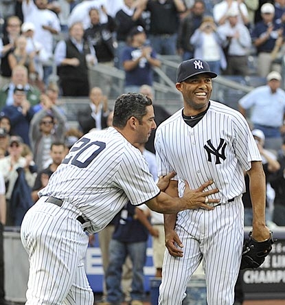 Longtime teammate Jorge Posada pushes Mariano Rivera back to the mound for a final bow after becoming the career saves leader.  (AP)