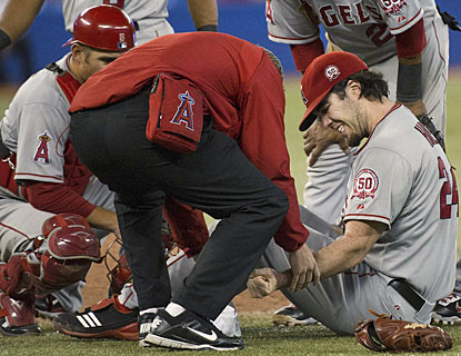 Dan Haren is tended to by an Angels trainer after being struck in the wrist by a shot from Eric Thames. (AP)