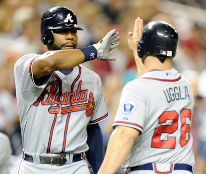 Dan Uggla (right) celebrates with Jason Heyward before finishing the game with three hits and two RBI. (Getty Images)