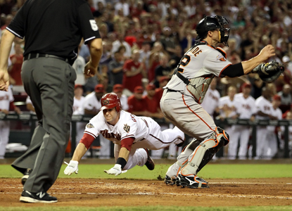 Paul Goldschmidt -- who lines a critical two-run triple in the eighth -- dives past catcher Eli Whiteside to score.  (Getty Images)