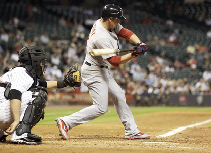 Ryan Theriot pivots toward a crucial two-run triple in the seventh which helps spark the Cardinals' victory.  (Getty Images)