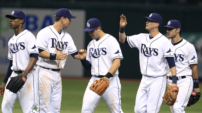 Evan Longoria (middle) and the Rays celebrate a much-needed win against the Yankees. (AP)