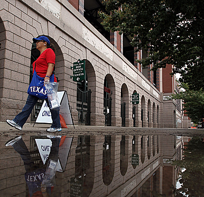 A Rangers fan walks around a puddle at Rangers Ballpark in Arlington, Texas, after Game 2 was postponed. (Getty Images)