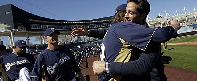 Braun gets a hello from teammate John Axford as other Brewers welcome the MVP to camp. (AP)