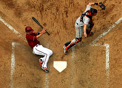 The Diamondbacks' Aaron Hill slides safely past the Giants' Buster Posey for a run in the seventh inning. (Getty Images)