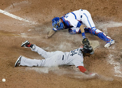 Catcher J.P. Arencibia fails to tag out Darnell McDonald, who represents the go-ahead run for Boston in the ninth inning. (AP)