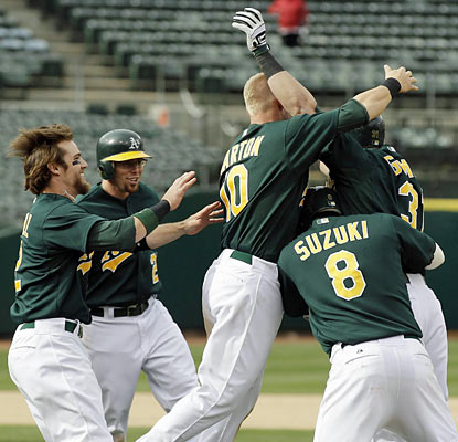Oakland celebrates after Kansas City hits a batter with bases loaded in the 12th inning. (AP)