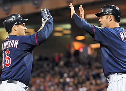 Joe Mauer (right) congratulates Josh Willingham, who hits a two-run home run as part of a three-run fourth inning. (AP)