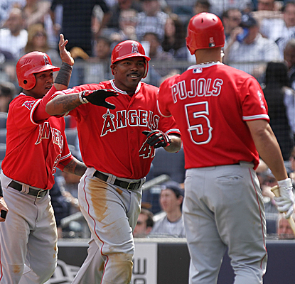 Albert Pujols welcomes home Howie Kendrick after the Angels 2B hits a 3-run shot in the fourth inning at Yankee Stadium. (Getty Images)