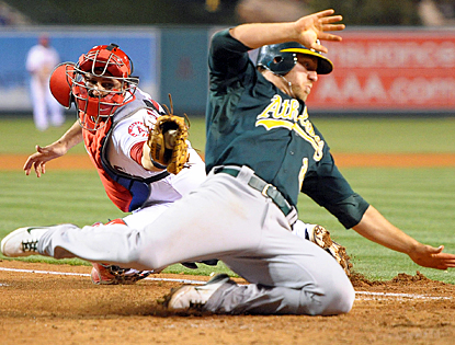 The Athletics' Cliff Pennington slides past the Angels' Chris Iannetta to score in the eighth inning. (US Presswire)