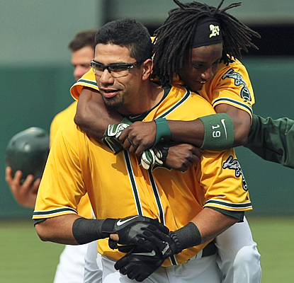 Kila Ka'aihue gets mobbed by a jubilant Jemile Weeks after his game-winning hit in the 14th against the White Sox. (US Presswire)