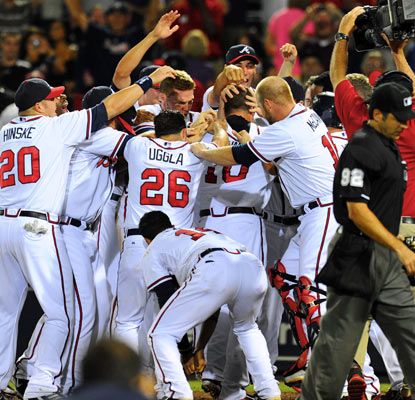 The Braves mob Chipper Jones after he ends the highest-scoring extra-inning game since 2006.  (US Presswire)
