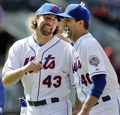 R.A. Dickey shares a laugh with reliever Tim Byrdak while celebrating his victory over Arizona.  (AP)