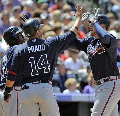 Freddie Freeman (right) has a greeting party after hitting a three-run homer to help the Braves to a sweep in Colorado.  (AP)
