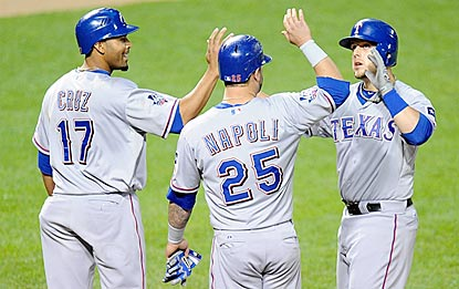 Veterans Nelson Cruz and Mike Napoli greet rookie Brandon Snyder after they score on his three-run blast in the sixth.  (Getty Images)