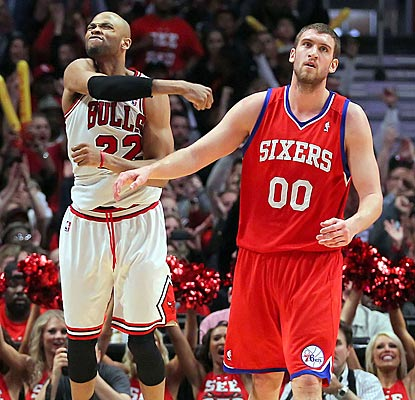 Taj Gibson celebrates while Sixers center Spencer Hawes laments a missed opportunity to knock out the injury-plagued Bulls.  (US Presswire)