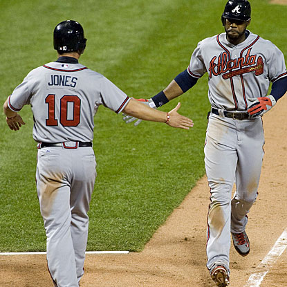 Jason Heyward (right) is greeted by Chipper Jones after hitting the two-run home run in the 12th inning. (US Presswire)