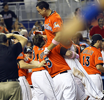 Giancarlo Stanton gets hoisted into the air by teammates after hitting a walk-off grand slam against the Mets. (AP)