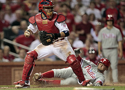 Freddy Galvis slides in safely for a run behind catcher Yadier Molina in the fifth inning. (AP)