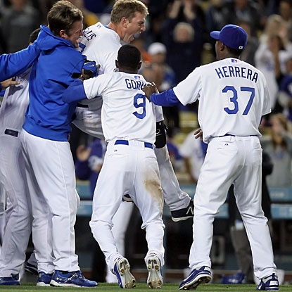 Teammates celebrate with A.J. Ellis (jumping) who propels Los Angeles to the win with a three-run homer. (Getty Images)