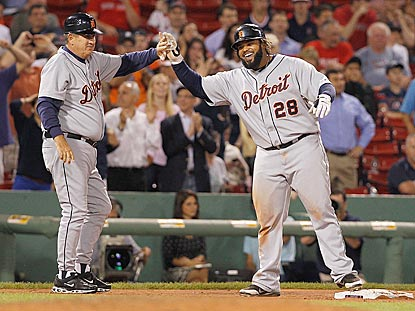Prince Fielder shares a laugh with third-base coach Gene Lamont after hitting a triple in the ninth inning. He later scores.  (Getty Images)