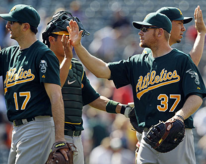 Brandon Moss (front right), who drives in three runs, celebrates Oakland's win with his teammates. (AP)