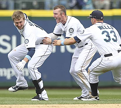 Justin Smoak's teammates chase him down after he delivers a walk-off single in the ninth inning.  (Getty Images)