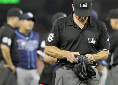 Umpire Chris Guccione confiscates and examines the glove of Rays reliever Joel Peralta, who gets ejected for having pine tar. (AP)