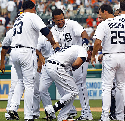 Winning pitcher Joaquin Benoit and Miguel Cabrera give Quintin Berry hearty slaps on the back after his game-winning hit.  (US Presswire)