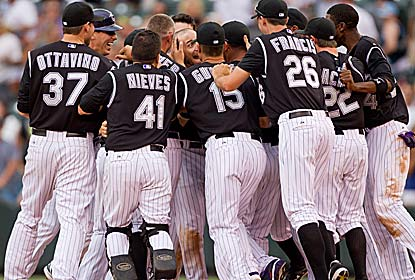 Mobbed Marco Scutaro is the hero after hitting an RBI single with two outs in the 11th for the Rockies, who blow a 7-0 lead. (Getty Images)