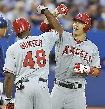 Torii Hunter congratulates Mike Trout on his home run in the sixth inning. The two-run blast breaks a 6-6 tie.  (Getty Images)