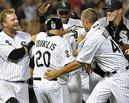 Kevin Youkilis is mobbed by his teammates after hitting the game-winning RBI-single in the 10th inning. (AP)